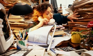 stressed worker with lots of files on desk