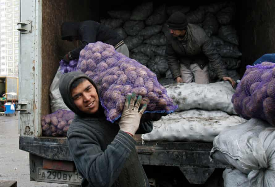Tajik migrant workers unload potato sacks at a vegetable market on the outskirts of Moscow