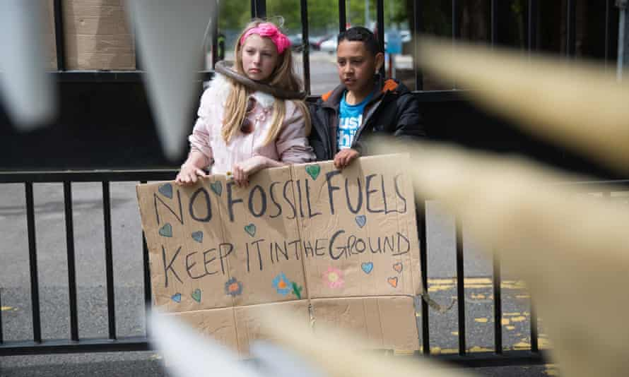 Seen through the teeth of a giant 'Cuadzilla', children stand behind a banner outside the gates of Didcot B power station as part of a protest against the fossil fuel industry by climate action group Reclaim The Power, Appleford, United Kingdom. 1st June 2015.