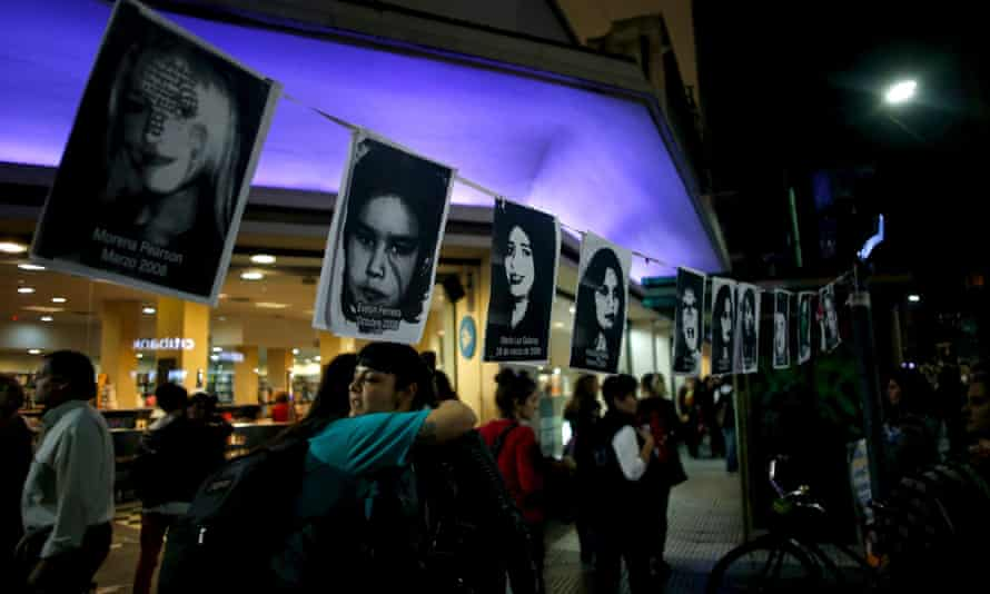 Women embrace under pictures of victims of gender violence during the Buenos demonstration.