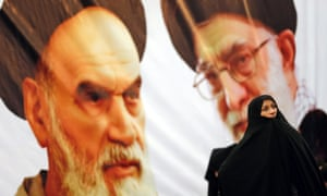 An Iranian woman wrapped in a chador stands in front of a huge poster with portraits of the late Ayatollah Khomeini, and Iranian supreme leader Ayatollah Khamenei (in glasses).