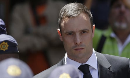 Oscar Pistorius is escorted by police officers as he leaves the high court in Pretoria, South Africa, last October.