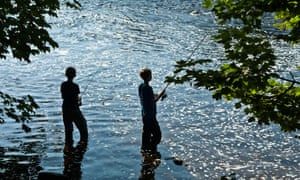 Two boy anglers fishing in a river.