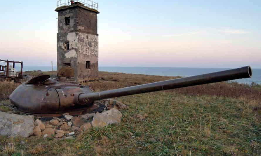 The turret of an old tank set in the ground  with a lighthouse in the background near Yuzhno-Kurilsk on Kunashir, one of the Southern Kuril Islands,
