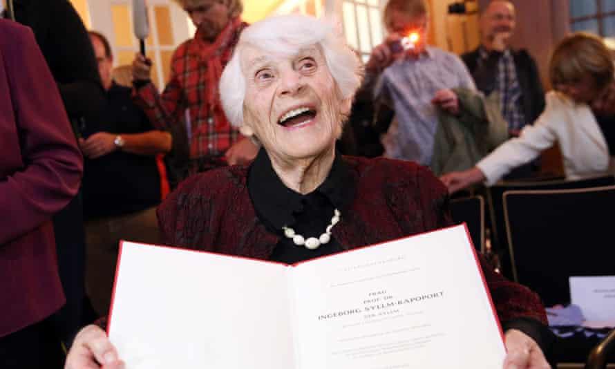 Ingeborg Syllm-Rapoport holds up her doctoral certificate.