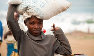 A young refugee carries part of the monthly food ration that the World Food Programme distributes to all inhabitants of the Mahama refugee camp in south-east Rwanda