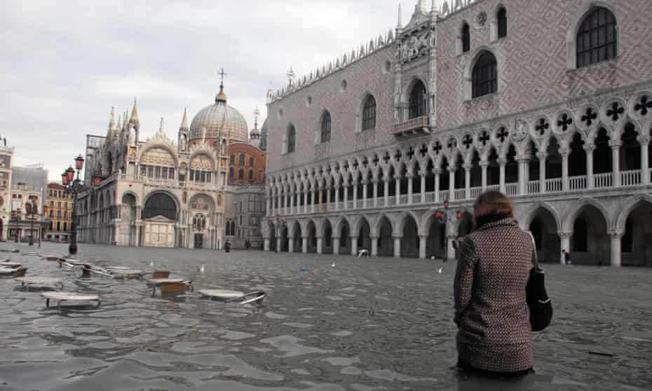 A woman walks through Piazza San Marco during a flood. Waters regularly reach above 130cm in the winter months.