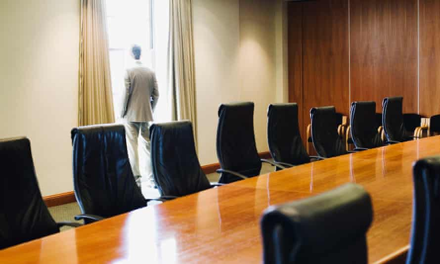 Man looking out of window in board room