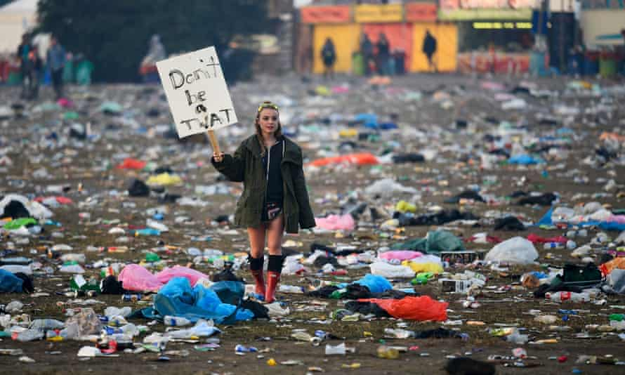A festival-goer walks through rubbish left in front of the Pyramid stage as they leave Worthy Farm.