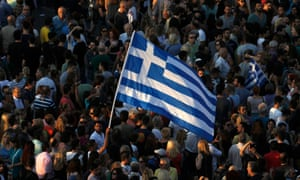 Protesters wave a Greek flag