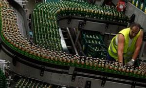 A worker adjusts bottles filled with Zlatopramen radler beer