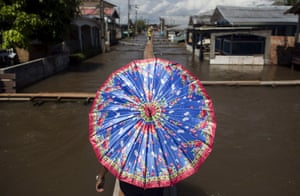Careiro da Varzea, Brazil A resident walks on a makeshift walkway above a street flooded by the rising Rio Solimoes, one of the two main branches of the Amazon River