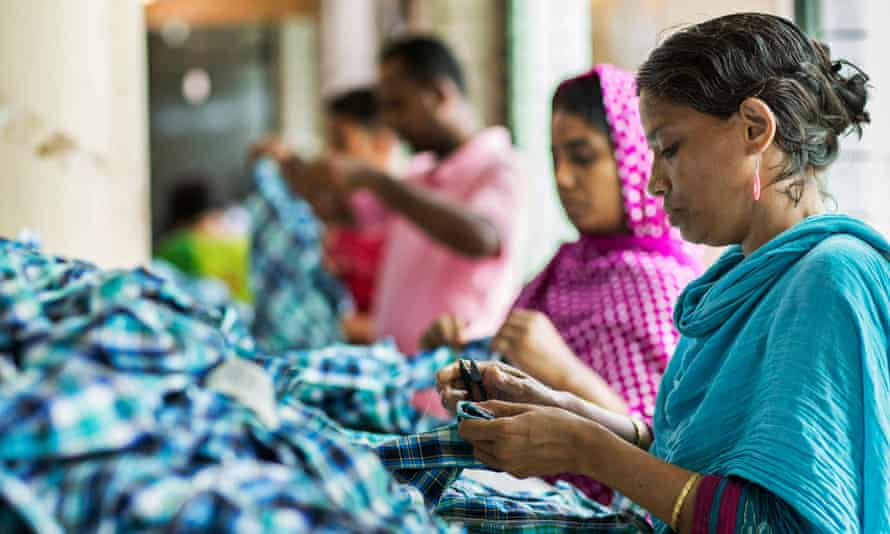 A garment worker cuts thread in Dhaka, Bangladesh
