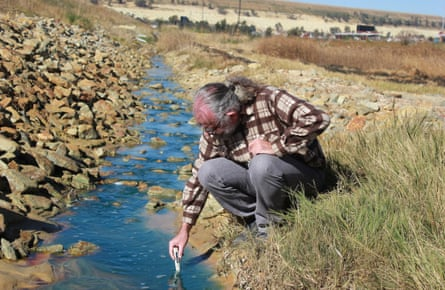 David Van Wyk, research director of charity Bench Marks, tests water in a run-off canal in Soweto.