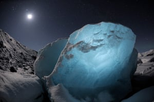 """James Balog, Jökulsárlón, Iceland, 2 March 2009, Washed up on the shore of a saltwater lagoon, an """"ice diamond"""" catches the light of the moon. Digital Chromogenic print, 26.5 x 40"""", Open edition."""