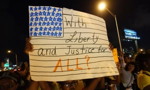 A woman holds a 'With liberty and justice for all?' sign as people blocked the I-195 freeway in Miami during Art Basel to protest the killings of Mike Brown, Eric Garner, and Israel 'Reefa' Hernandez in Miami Beach.