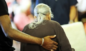 An elderly Sikh lady is helped to her chair in a multicultural extra Care home Bradford West Yorkshire.