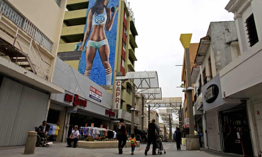 People walk through a shopping area in San Juan, Puerto Rico, where many businesses have closed.