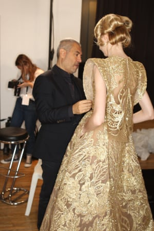 Elie Saab speaks to a model backstage wearing one of his latest Game of Thrones-style creations.
