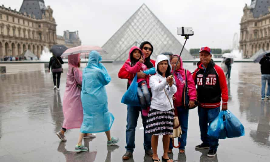 Tourists take a selfie near the Pyramid of the Louvre Museum on a rainy summer day in Paris.