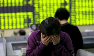 An investor covers her face in a stock exchange hall in Nantong, Jiangsu province, China, during the recent week of turbulence.