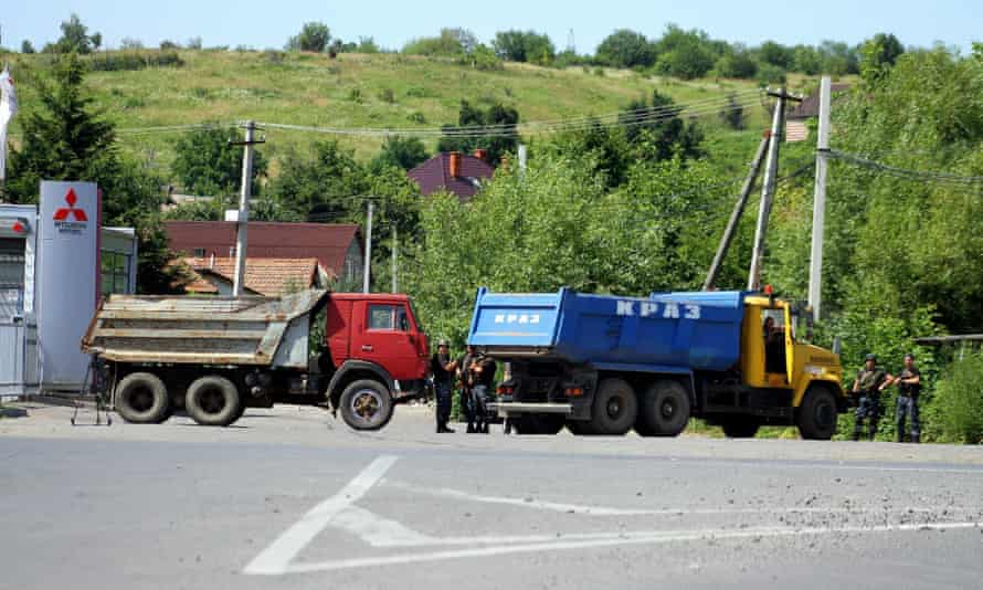 Ukrainian servicemen guard entrance to the western city of Mukacheve, after fighting between police and Right Sector fighters took place on Saturday.