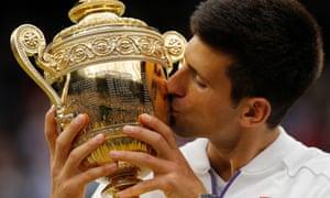 Novak Djokovic kisses the trophy after his victory over Roger Federer.