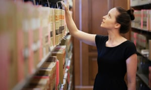 Woman searching through books in library
