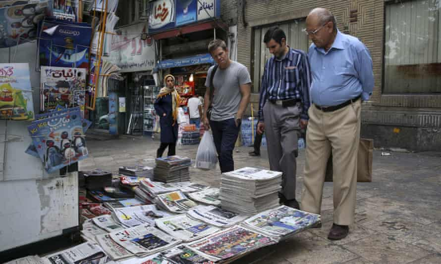 People read the front pages of Iranian newspapers at a newsstand in Tajrish Square, northern Tehran, Iran.