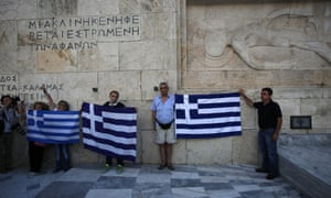 Anti-austerity protesters hold Greek flags during a rally against the government's agreement with its creditors.
