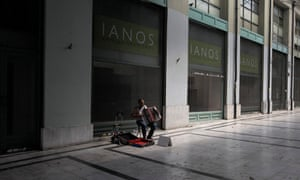A street musician plays the accordion in an arcade in central Athens where shops are closed due to recession.