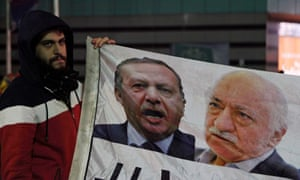A demonstrator hold pictures Recep Tayyip Erdogan (left) and Fethullah Gulen, during a protest against Turkey's ruling AK party in 2013.