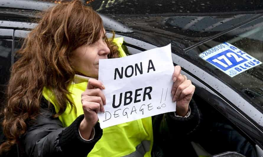 A taxi driver holds a sign reading 'no to Uber, get out!'