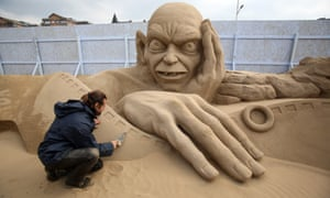 Man making a sand sculpture of Golem.