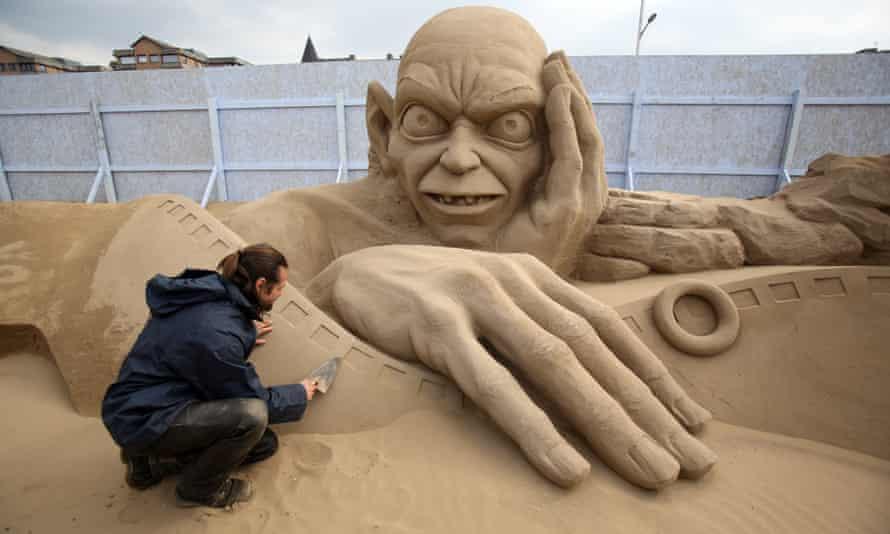 Man making a sand sculpture of Golem.