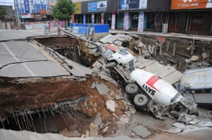 Chuzhou, China A cement mixing truck lies on its side after a road collapsed
