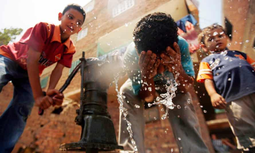 Children drink water and wash from a hand pump in Qalyoubia village north of Cairo.