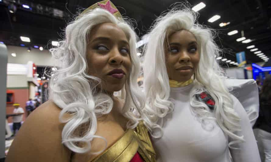 Cosplay enthusiasts Liz (L) and Ruth wear costumes resembling Wonder Woman and Storm from the X-Men.