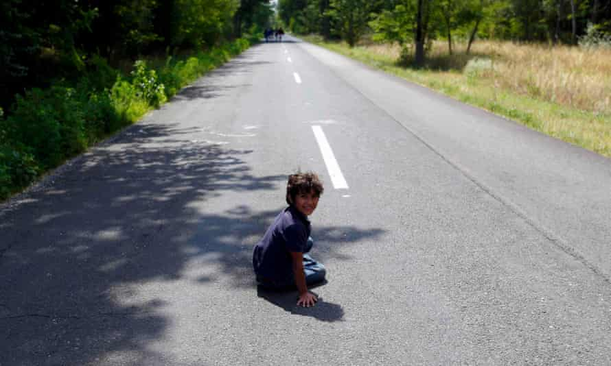 A migrant boy from Syria rests on a road after crossing illegaly the border of Serbia to Hungary, near Asotthalom, Hungary on 14 July 14, 2015.