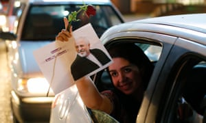 An Iranian woman holds a flower and a poster of Iranian foreign minister Mohammad Javad Zarif