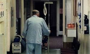An elderly patient attached to a drip walks along a hospital corridor