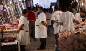 Butchers wait for clients in a meat market in central Athens. Capital controls and bank closures have damaged the Greek economy far more than thought, a leaked IMF report states.
