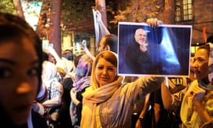 A woman holds a poster of the Iranian foreign minister as people in Tehran celebrate the nuclear deal.