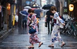 Women in kimonos run through the rain in Kyoto, Japan