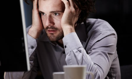 Stressed man looking at computer screen