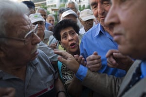 Pensioners wait for a bank to open in Athens, Greece