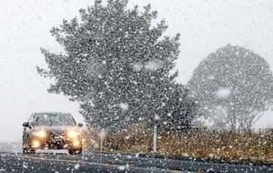 A motorist drives through an early morning snow shower in Orange, Australia