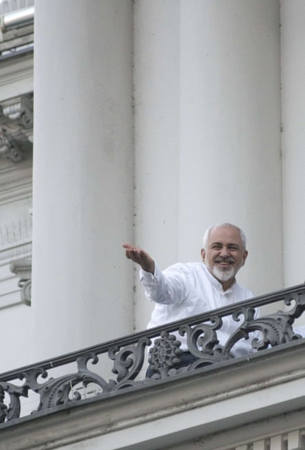 Iranian foreign minister Mohammad Javad Zarif gestures towards reporters from a balcony of the Palais Coburg Hotel.