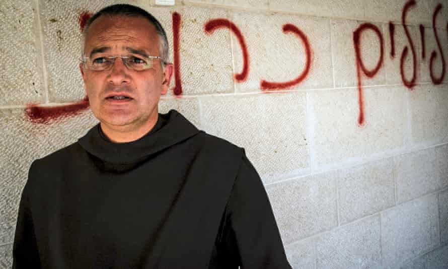 """Fr Matthias stands in front of Hebrew graffiti calling for the """"destruction of false idols""""."""