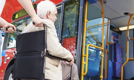 Man in wheelchair being pushed on to bus